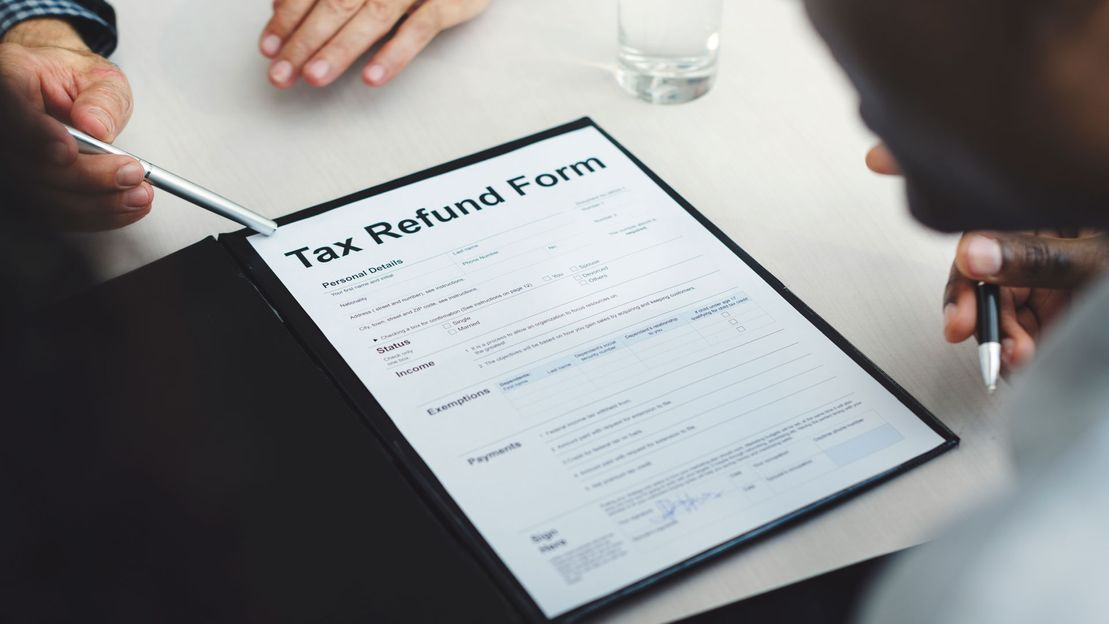 A man showing someone a tax refund form